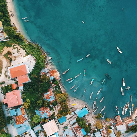 Aerial view of buildings by boats moored on sea