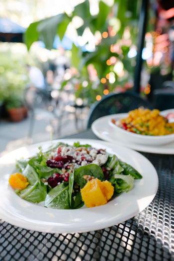 Healthy salad on a restaurant patio table with plants in the background. Lunch Summer Garden Dining Table Day Salad Outdoors Restaurant Healthy Vegetables Vegetarian Patio Vegetarian Food Freshness Plate Bowl Close-up Al Fresco Healthy Eating No People Arugula Salad Bowl
