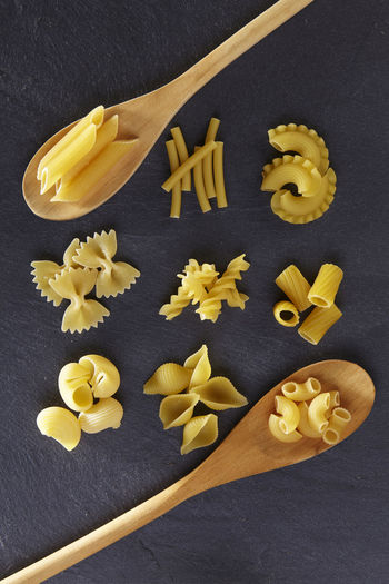 Variety of types and shapes of Italian pasta Black Background Dried Food Food And Drink Freshness Spaghetti Assortment Carbohydrate - Food Type Directly Above Food Healthy Eating High Angle View Indoors  Italian Food Large Group Of Objects Macaroni No People Pasta Raw Food Slate Still Life Studio Shot Table Variation Variety Yellow