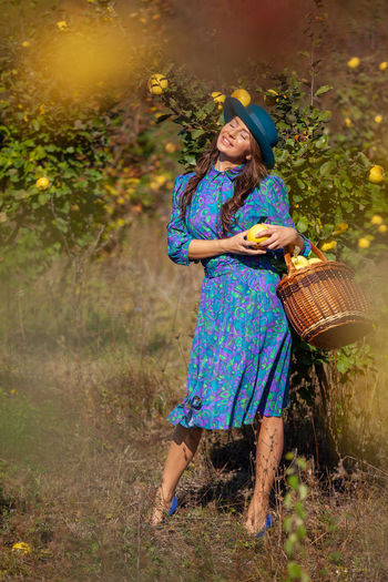 Smiling woman with fruits standing on land