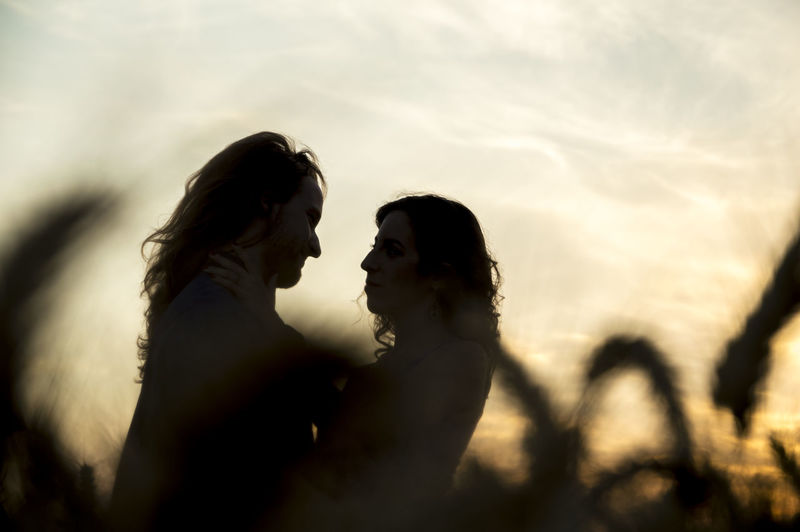 Silhouette Couple At Farm Against Sky During Sunset