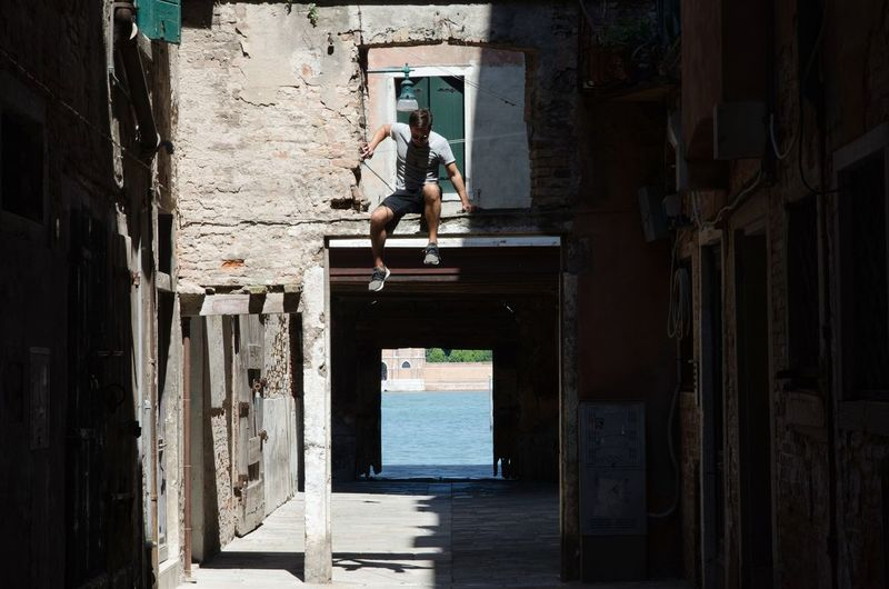 Full length of man jumping from old built structure in old town