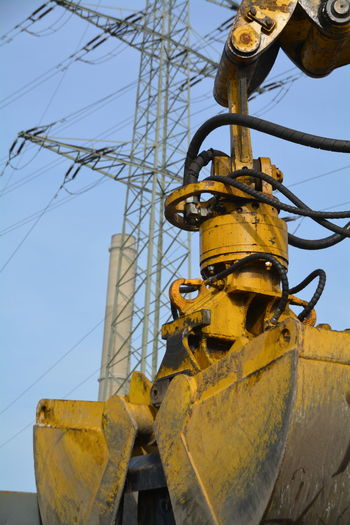 Close-up of construction machine with electricity pylon in background