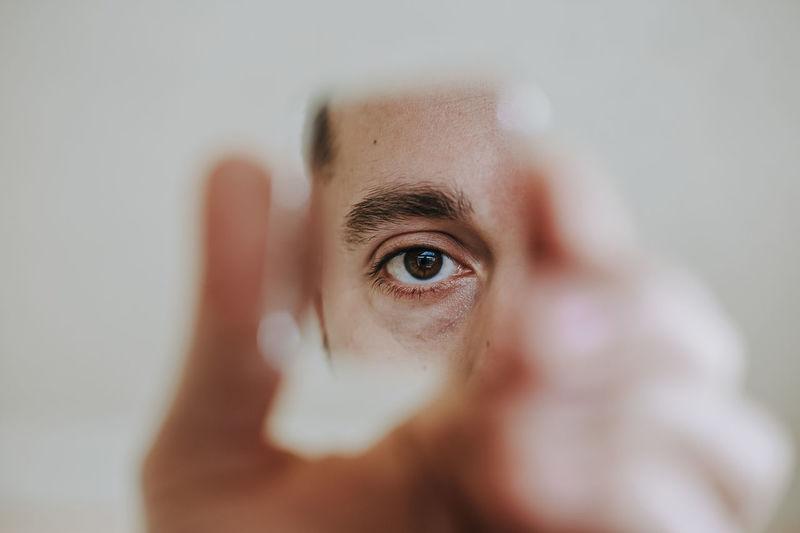 Close-up eye looking into broken mirror