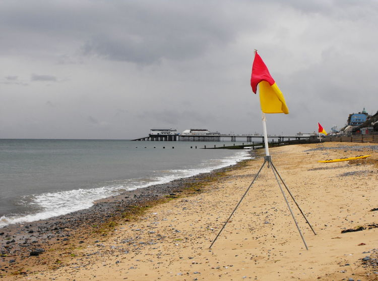 Cromer, British weather Water Sea Sky Cloud - Sky Beach Land Flag Nature Horizon Horizon Over Water Day Outdoors Sand Scenics - Nature Overcast Beauty In Nature No People Tranquility Flags Pier Cromer Red And Yellow Britain Dark Clouds British Seaside