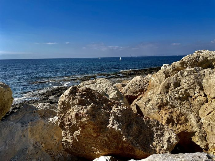 Scenic view of rocks on beach against blue sky