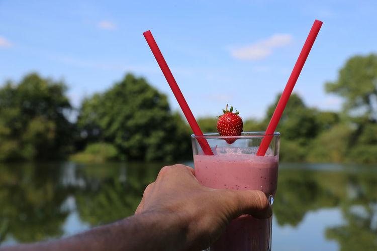 Close-up of hand holding strawberry milkshake against water