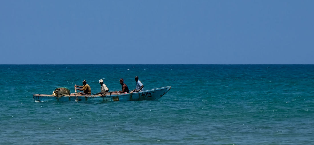 Fishermen with the days catch Autentic Moments Caribbean Life Dominican Republic Row Boat Rowing Beach Caribbean Day Fisher Men Fishing Boat Group Of People Men Nature Nautical Vessel Ocean Outdoors Sea Sea And Sky Transportation Water Waterfront