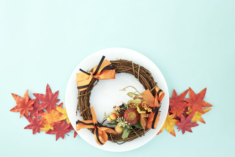 White dish with wreaths and autumn leaves decorative Halloween on pastel pale blue background, with copy space for text. Flat lay. Sales Holiday Flyer Banner Poster Travel Traveling Traveler Vacation Trip Sale Template Mockup Abstract Art Autumn Leaves Falling 2019 2020 Wreath New Year Halloween Autumn Leaves Autumn Background Plate Minimal Flat Lay Fall Background Leaf Design Frame Orange Concept Composition Green Maple Bright Pattern Forest Decoration Studio Shot Plant Part Indoors  No People Nature White Background Still Life Copy Space Plant Close-up Cut Out Food Food And Drink Table Freshness Change High Angle View Maple Leaf