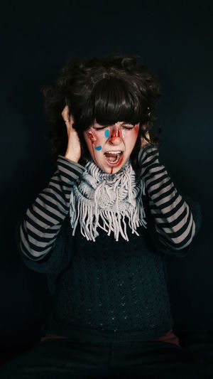 Adult Adults Only Black Background Casual Clothing Front View Fun Halloween Hands Covering Ears Human Body Part Human Mouth Indoors  Looking At Camera Mouth Open Night One Person People Portrait Screaming Shouting Striped Studio Shot Young Adult