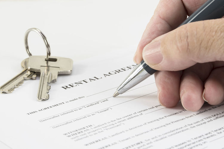 Close-up of hand filling rental agreement by house key