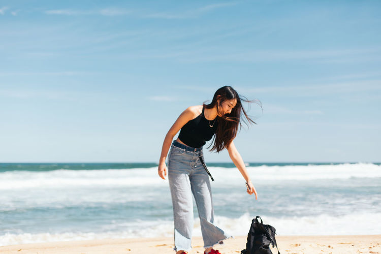 Young woman picking bag while standing at beach against sky during sunny day