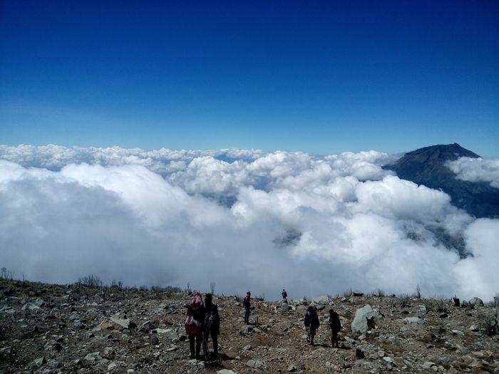 High angle view of people standing on mountain by cloudscape