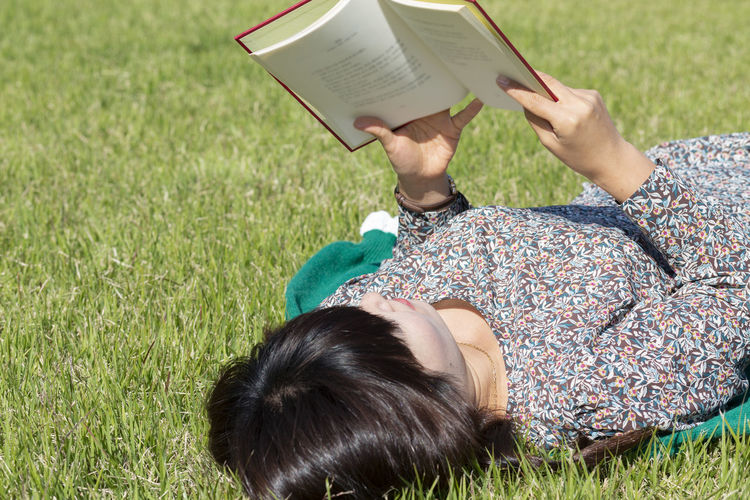High angle view of woman reading book on field