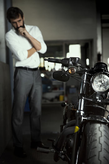 Focus On Foreground Motorcycle Working Front View One Person Occupation Men Indoors  Standing Worried Thinking Concern Concerned Bike Bikers Motorbike Motorbikestyle darkness and light