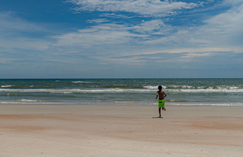 Rear view of boy running at beach against sky