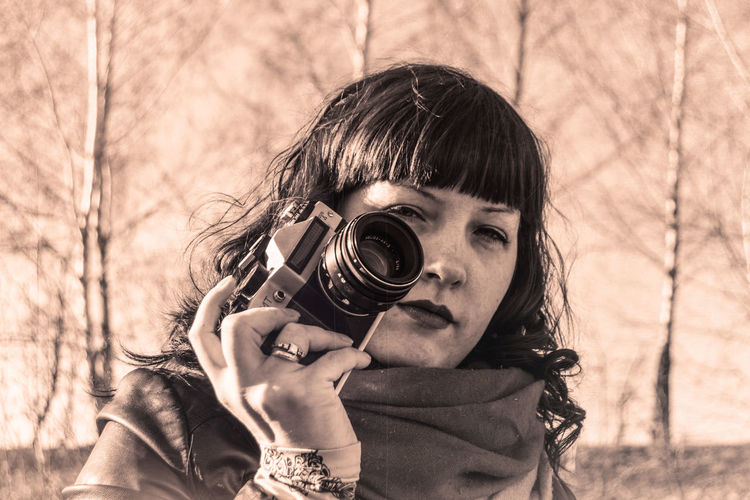 Portrait of woman holding camera against bare trees