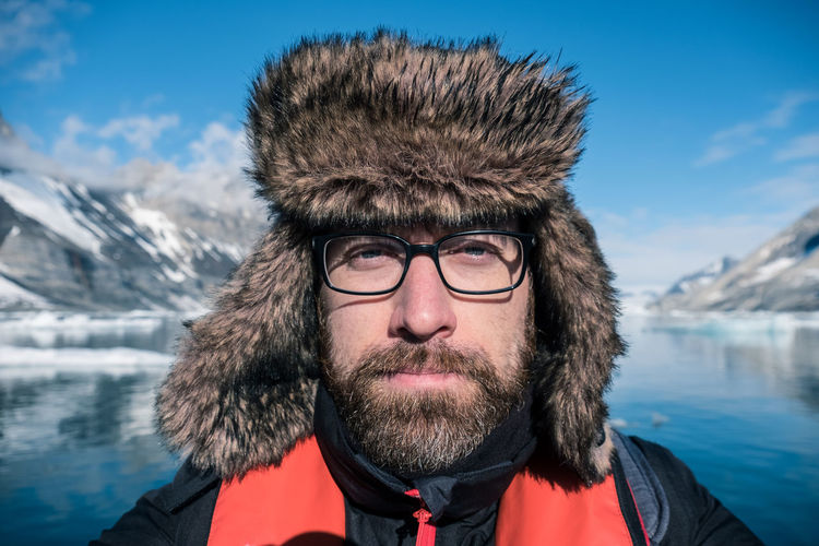 Portrait Of Mid Adult Man Against Lake During Winter