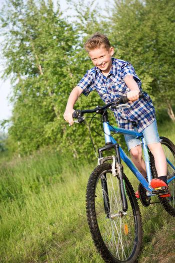 Smiling boy cycling on grassy field