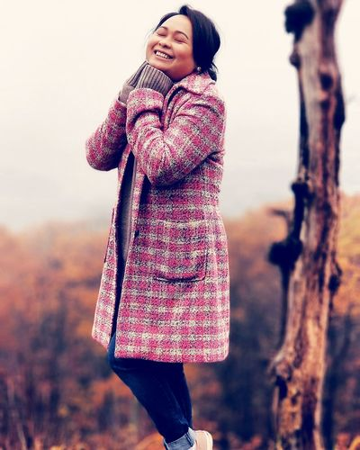 Smiling mid adult woman with eyes closed standing against trees