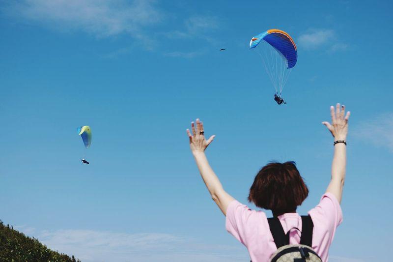 Rear view of women flying against sky