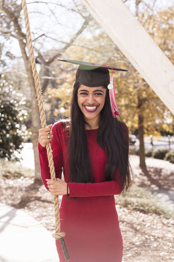 Portrait of laughing young woman wearing mortarboard while holding rope