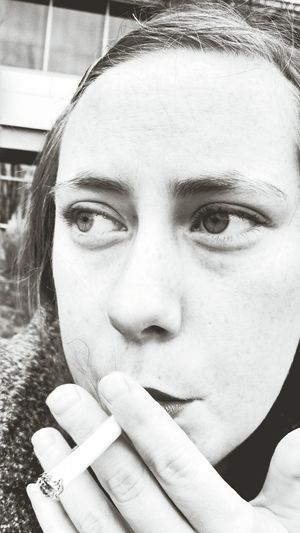 Close-up of thoughtful young woman smoking outdoors