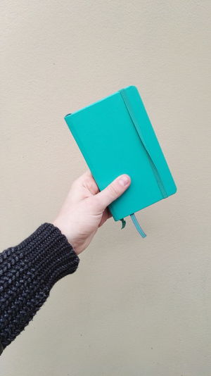 Close-Up Of Hand Holding Diary Against Wall