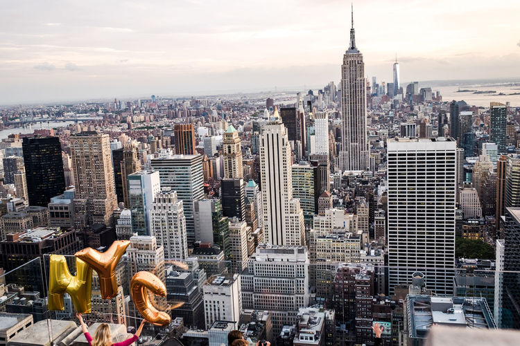 Rear view of woman holding alphabet balloons against empire state building in city