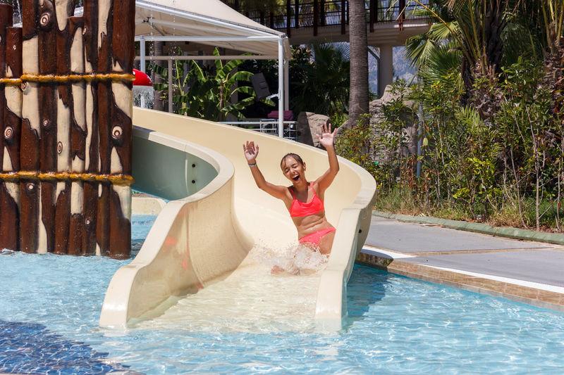 Happy woman in slide at pool