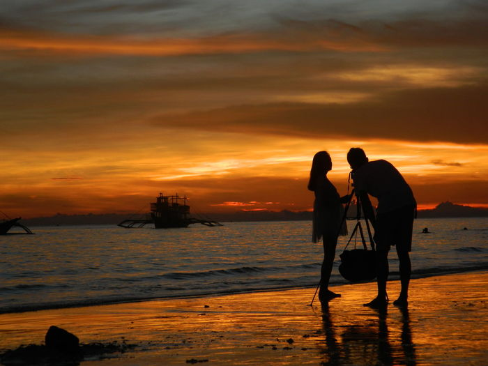 Silhouette couple photographing at beach against sky during sunset