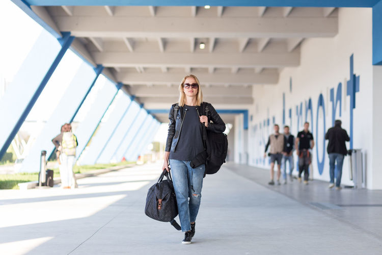 Full length portrait of young woman walking on airport