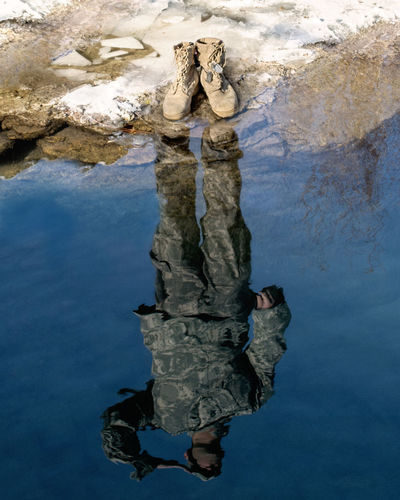 Reflection of soldier saluting on lake