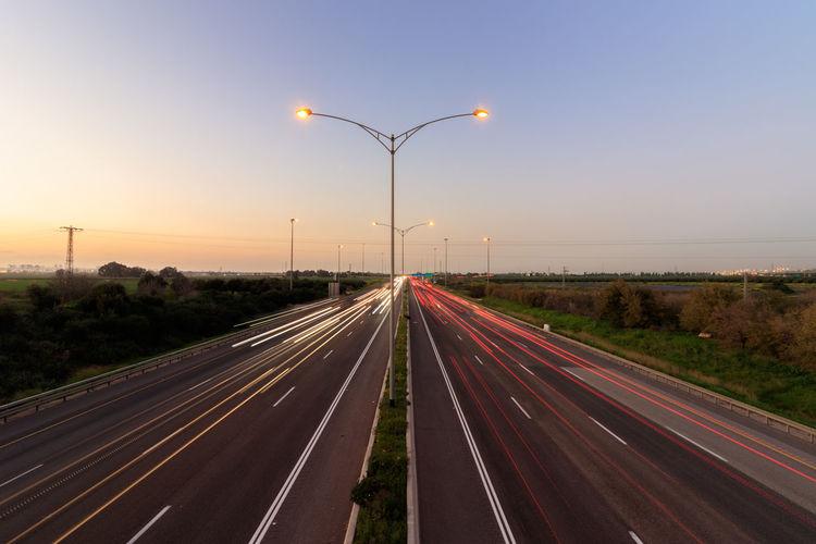 Light trails on highway against sky