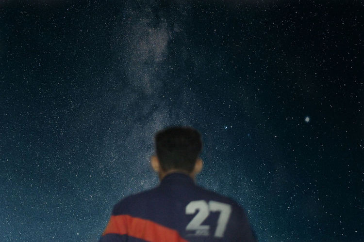 Rear view of man against star field