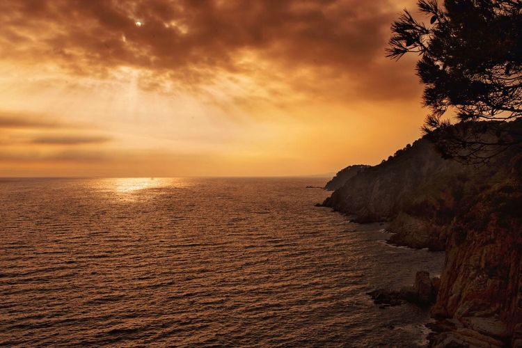 Scenic view of sea against cloudy sky at sunset