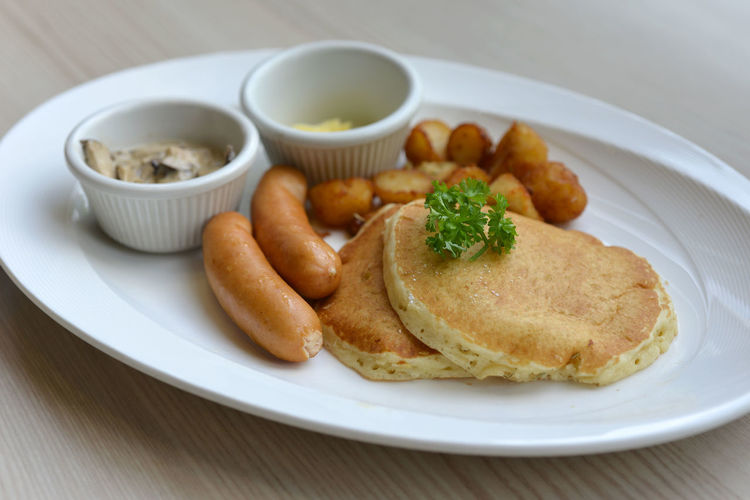 Close-up of pancakes with sausages served on table