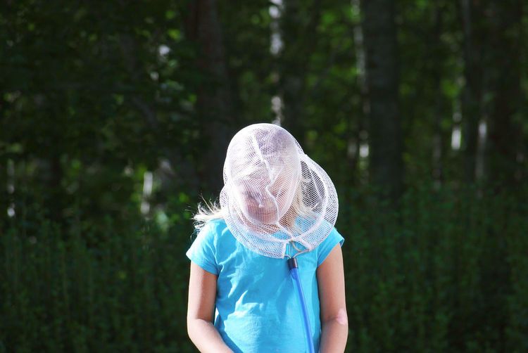 Girl wearing butterfly net on face while standing in forest