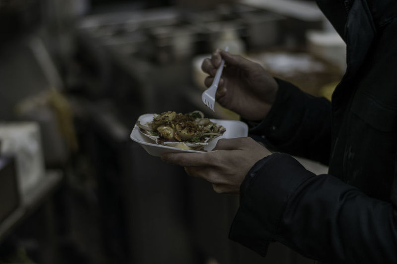 Midsection of man eating food while standing on street