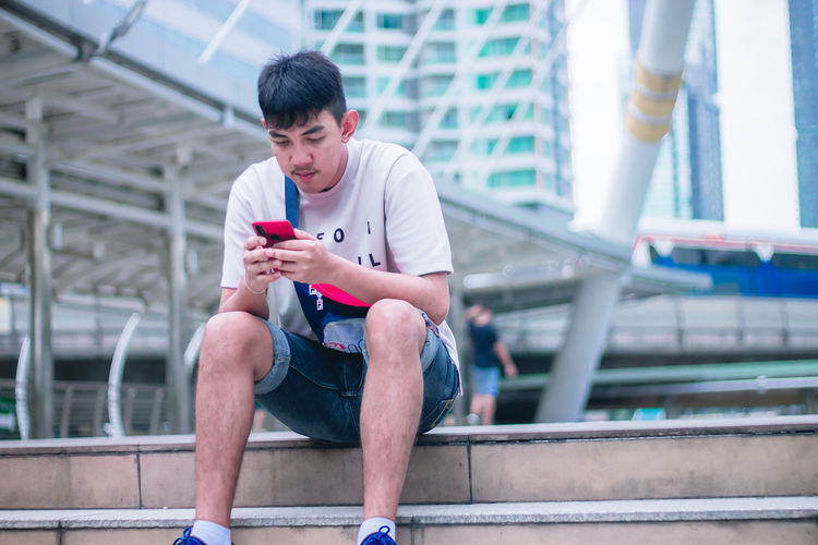 One Person Mobile Phone Sitting Wireless Technology Technology Young Men Young Adult Portable Information Device Text Messaging Smart Phone Connection Communication Front View Architecture Holding Real People Using Phone Day Casual Clothing Lifestyles Outdoors Receiving