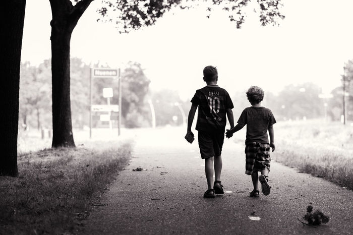 Together in the search for Pokemon! Blackandwhite Boys Brothers Clear Sky Holding Hands Into The Light Looking For Pokemons Outdoors Rear View Serenity Summer Sunlight The Way Forward Togetherness Tranquility Tree Trunk Walking The Street Photographer - 2017 EyeEm Awards