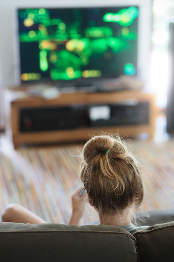 Back view of young girl playing video game sitting on sofa at home Fun Home Playing Games Real Relaxing Screen Child Childhood Console Game Girl Home Interior Indoors  Lifestyles One Person People Person Playing Real People Rear View Sitting Technology Teenager Tv Video
