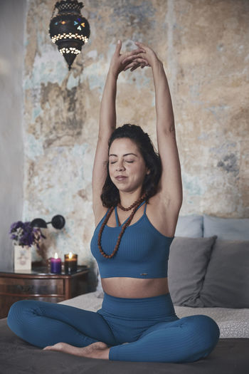 Woman exercising while sitting on bed at home