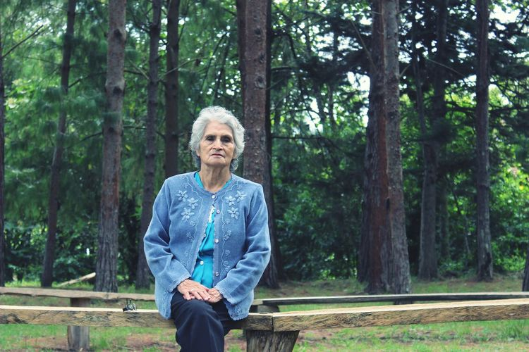 Senior Woman Sitting On Wooden Seat Against Trees At Forest