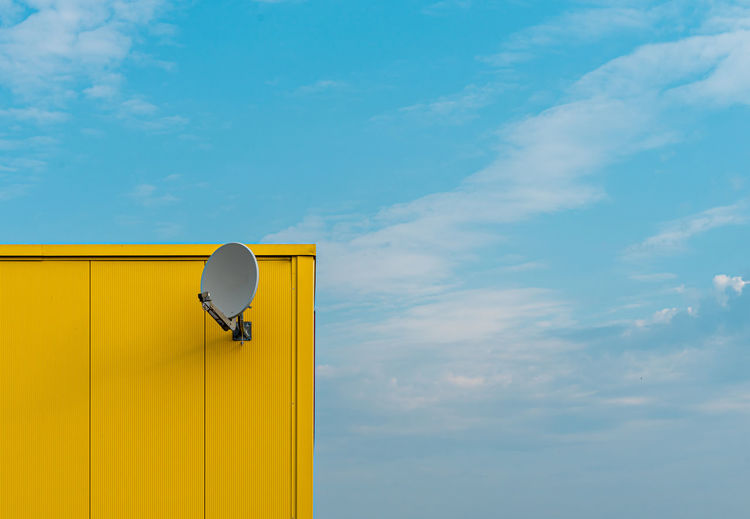 Low angle view of yellow building with satellite dish against sky