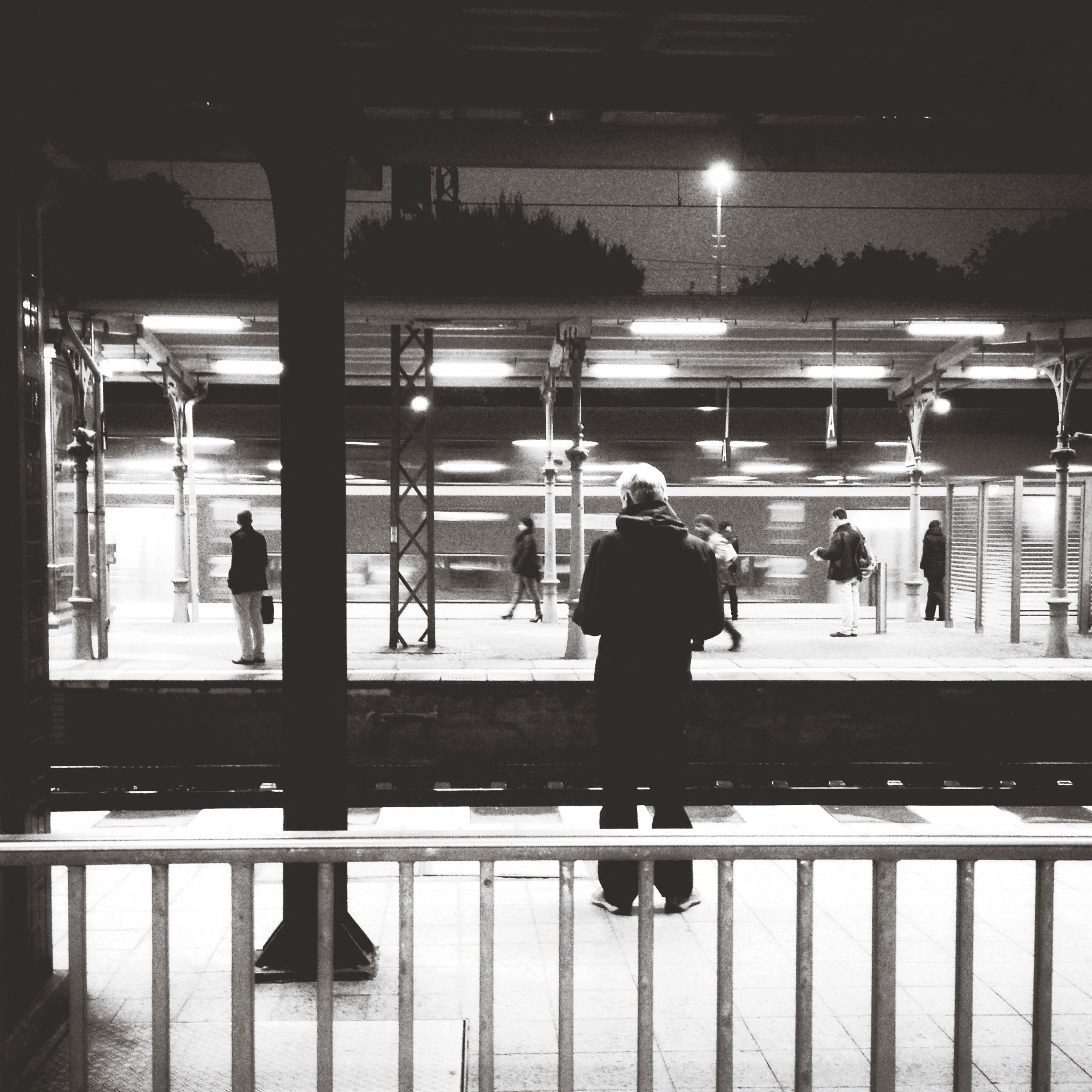 lifestyles, men, illuminated, person, leisure activity, night, full length, indoors, silhouette, city life, walking, railroad station platform, city, rear view, railroad station, built structure, standing, architecture, airport