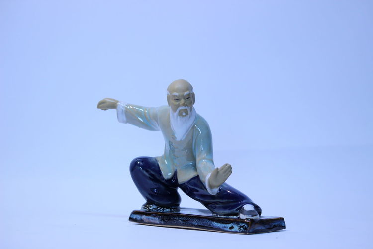 Male figurine performing tai chi against blue background