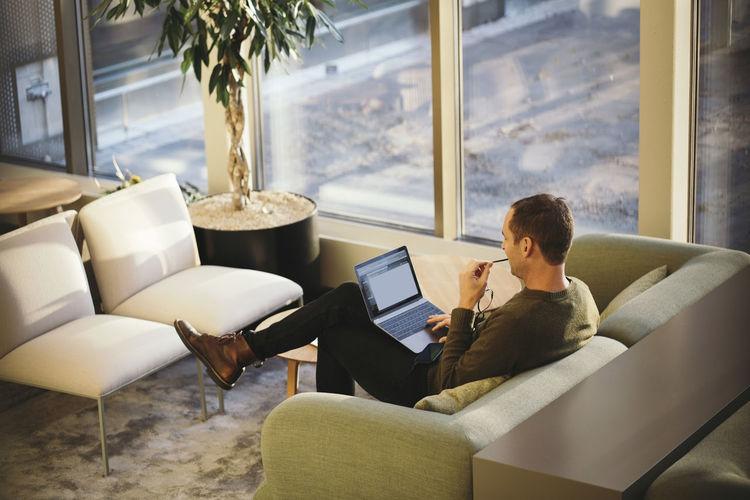 Man using laptop while sitting on sofa