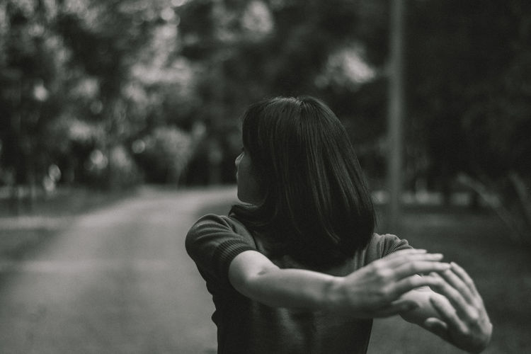 Rear view of young woman stretching while standing on footpath in park