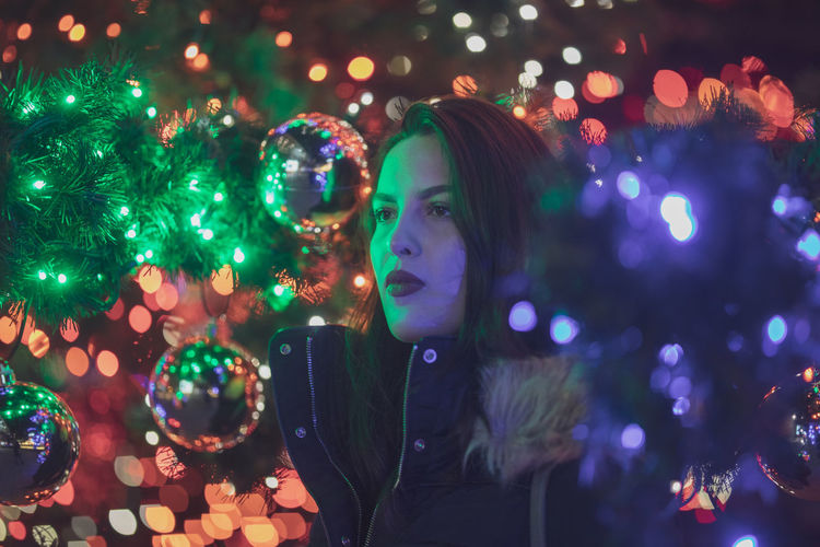 Thoughtful young woman standing against illuminated christmas tree at night